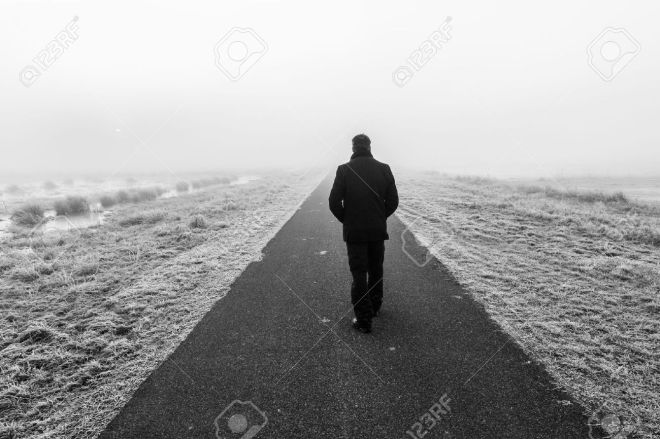 35957453-man-walking-away-on-an-empty-desolate-raod-stock-photo
